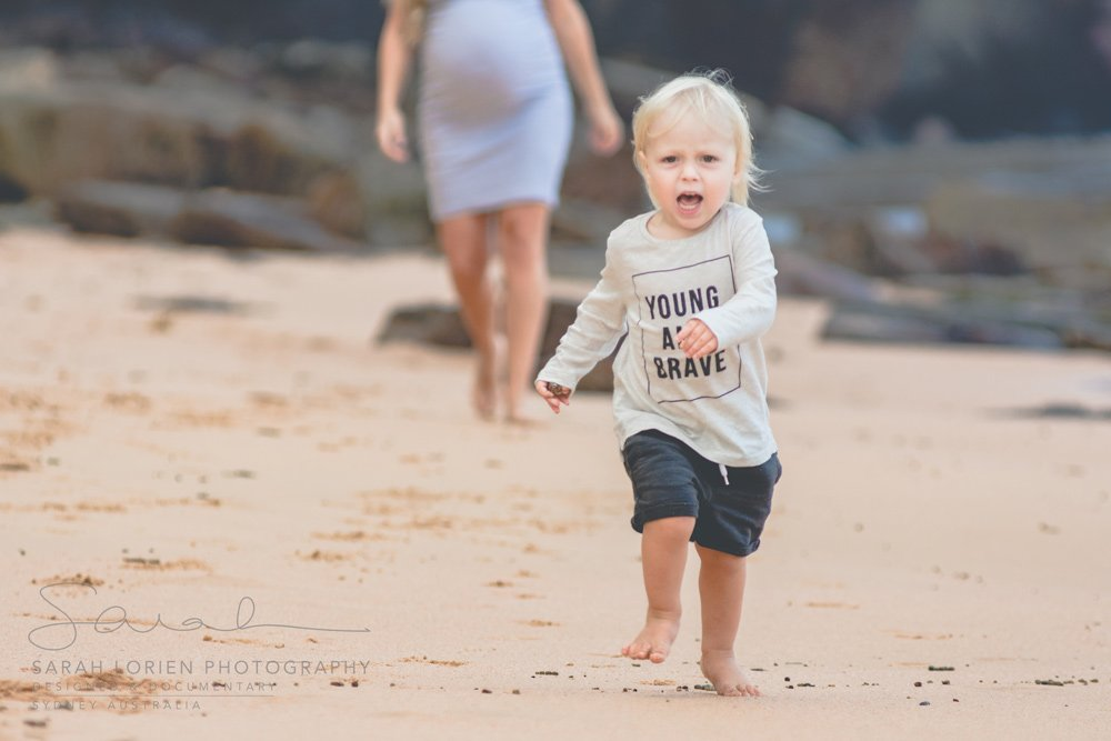 young child running towards camera at the beach